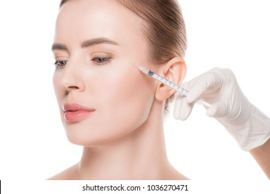 Beautician hands doing injection in woman cheek isolated on white