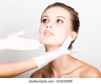 beautician hand's examining beautiful young female face.