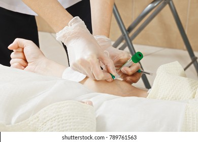 Beautician hands taking blood from vein, which will be used in plasma needling sking rejuvenation procedure. Horizontal closeup shot