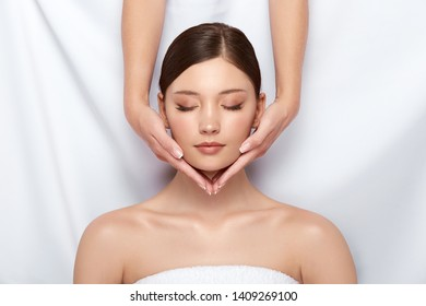 beautician holding woman's face with her eyes closed, pure fresh and healthy female skin, massaging and relaxation for women