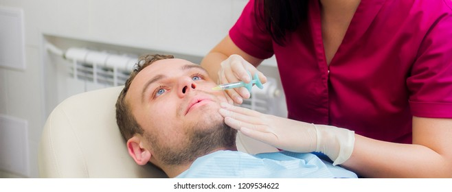Beautician injects a man for facial rejuvenation