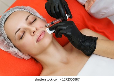 Beautician makes beauty injections next to nose on face of woman. Smoothing of mimic wrinkles. Beauty therapy. Cosmetic procedure in spa salon.