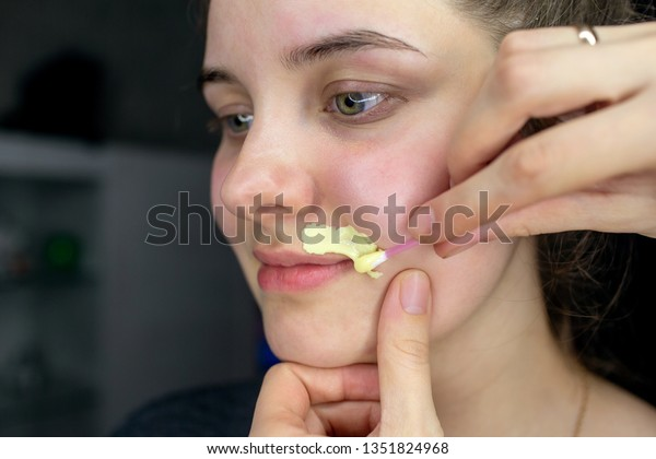 Beautician  makes depilation with hot wax mustache and eyebrow correction on a black isolated background