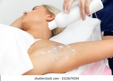 beautician makes depilation underarms of the client lying on a pink couch in a beauty salon. beautician pour talcum powder from the bottle. slow motion