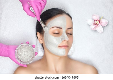 Beautician makes a face clay mask against acne on the face of a woman to rejuvenate the skin. treatment of problem skin on the face and body. Cosmetology and professional skin care.