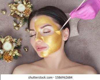 Beautician makes a golden mask to rejuvenate the skin to beautiful woman. Next to her are Christmas decorations.New Year's and Cosmetology concept.