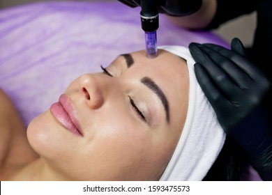 Beautician makes mesotherapy injections. Microneedle mesotherapy. Treatment of a woman by a beautician. Hardware cosmetology. Mesotherapy, facial area treatment, facial rejuvenation. face and forehead