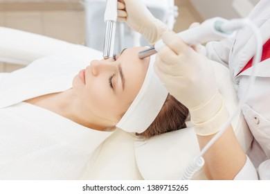 Beautician makes a microcurrent massage of the face of the girl client with the help of modern salon equipment. The concept of hardware cosmetology