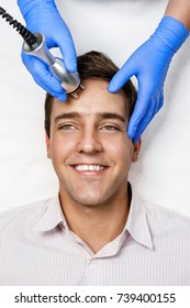 Beautician makes RF-lifting to young man. The cosmetic procedures for the face. Beauty treatments in the spa salon.