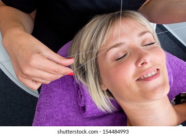 beautician makes threading hair removal procedure to blond woman in salon
