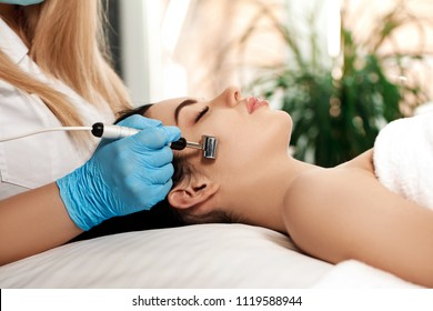 Beautician makes Ultrasonic cleaning of the face in spa salon. cosmetology
