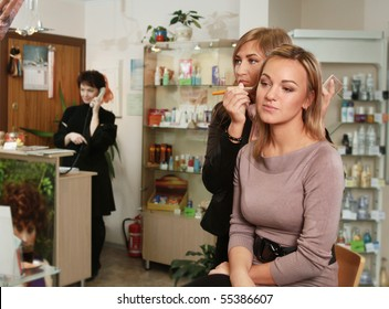 beautician making up young woman's face in salon