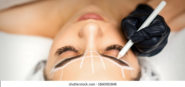 The beautician marks the eyebrow with a white pencil to prepare a permanent makeup procedure