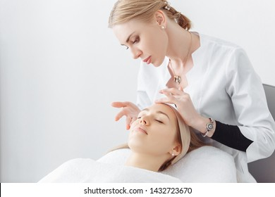 Beautician massage therapist making facial massage to a beautiful female client sitting on a couch in a cosmetology office. Skin care concept