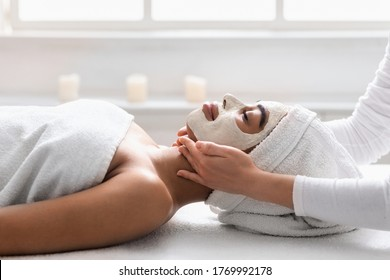 Beautician massaging black woman chin at spa, lady having white face mask, side view