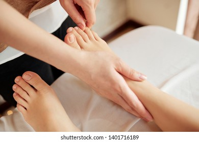 Beautician massaging feet on woman before doing pedicure