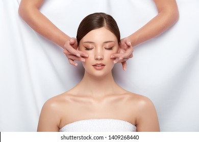 beautician massaging woman's cheeks on white, lovely girl having facial treatment, beautiful face receiving skin theraphy