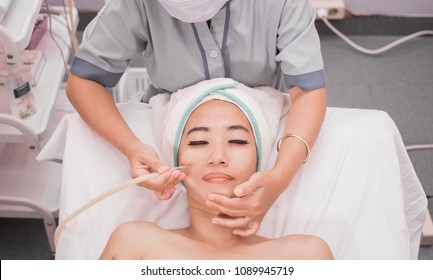 beautician perform beauty treatment on woman face. blackhead suction