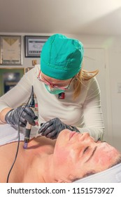 Beautician performs a needle mesotherapy treatment on a woman face.