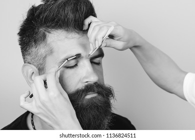 Beautician plucking beautiful bearded man eyebrows with tweezers in beauty salon. Close up of client man with beard relaxing while cosmetician epilating eyebrows using plucking tools in beauty spa