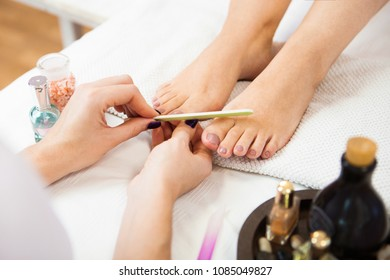 Beautician polishing nails, pedicure. Foot care treatment and nail, the woman at the beautician for pedicure.