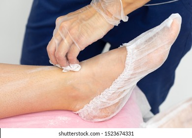 beautician pours talc on the legs of the client to prepare for epilation. the client is lying on a pink couch. slow motion