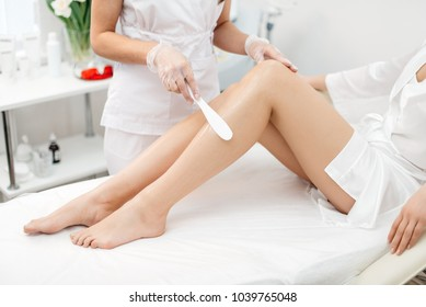 The beautician is preparing for depilation and applying the cream with wax stick on the beautiful female legs. Beauty salon.