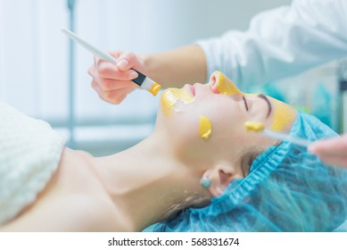 beautician puts gold facial mask for woman