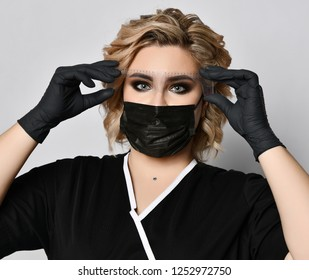 Beautician ready doing tattooing eyebrow permanent make-up for eyebrows of beautiful woman with thick brows ruler in beauty salon in black gloves and mask on gray background