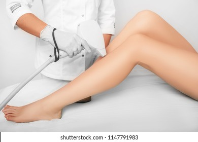 beautician removes hair on beautiful female legs using a laser. hair removal on the legs, laser procedure at clinic