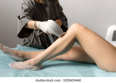 Beautician removing hair on slim female legs using a laser. Hair removal, laser procedure at clinic