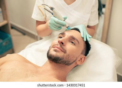 Beautician in rubber gloves holding a modern tool while nourishing the skin of a smiling man with intense moisturizers