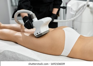 beautician treating woman buttoks with endosphere massager at beauty clinic