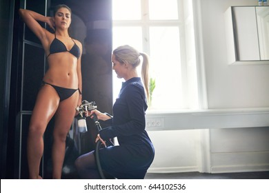 Beautician using aerograph for spray tan apply to young pretty female leg in beauty salon.