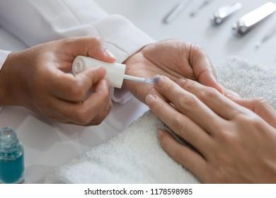 Beautician using a nail polish giving customer service a manicure at salon