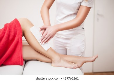 Beautician waxing woman a leg at salon / Depilation.