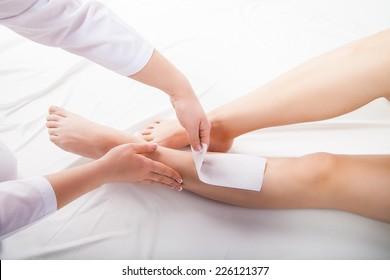 Beautician waxing  woman legs in a spa salon