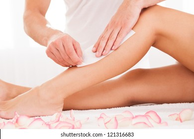 Beautician waxing a woman's leg applying a strip of material over the hot wax to remove the hairs when pulled