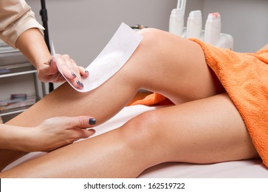 Beautician waxing a woman's leg applying a strip of material over the hot wax to remove the hairs