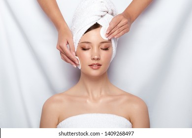 beautician wiping woman's face with cotton pads, girl gets facial treatment, female arms cleans body with two sponges in spa