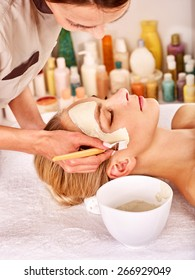 Beautician and woman  with clay facial mask in beauty spa.
