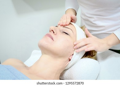 beautician worker gently massages face of  female costumer in beauty salon