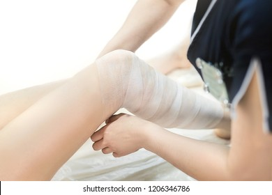 Beautician wraps the leg of the patient in a white bandage. Cosmetic procedure for weight loss: stimulates the metabolic processes of the triglycerides providing a slimming effect. Anti-cellulite
