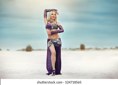 Beautidul smiling lady dancing Belly dance in the sands desert