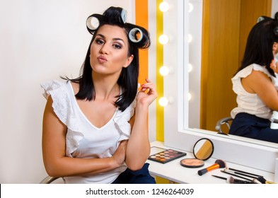 Beautification concept young woman with hair curlers puckering lips