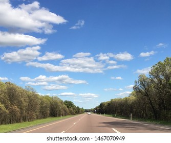 Beautifl blue sky with clouds that almost seem to make the sky look animated. the sky is met by trees on both sides of the road. the road itself is a representation of the future ahead.