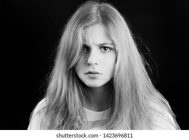 Beautiful 18 year old blond girl on a black background, Flers, France. Studio lighting. Black and white portrait. Hair detached, she has an angry dark mesmerizing look on her pretty face. May 2017