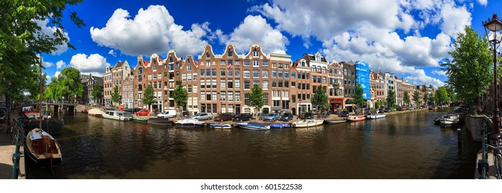 Beautiful 180 degree panoramic panorama of the UNESCO world heritage Prinsengracht canal  in Amsterdam, the Netherlands, on a sunny summer day with a blue sky and clouds