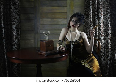 Beautiful 1930s girl smokes a cigarette at the table