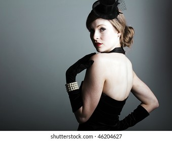 a beautiful 1930s styled woman in a little black dress, gloves and veil